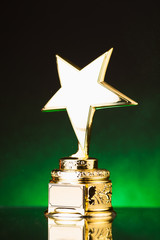 gold star trophy against  green illumination background