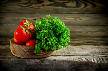 Fresh vegetables and herbs, tomatoes and parsley on a wooden tab