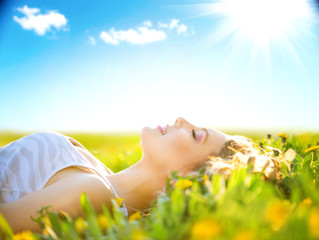 Beautiful healthy girl lying on summer field with flowers