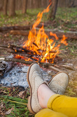 Recreation scene: woman feet in light brogues by camp fire