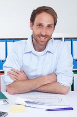Lachender Kaufmann mit Bart im Büro