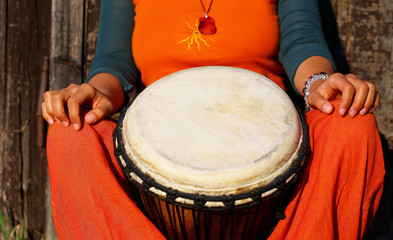 Young lady drummer with her djembe drum on rustic wooden door