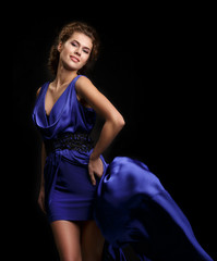 Woman in blue dress with flying silk fabric.