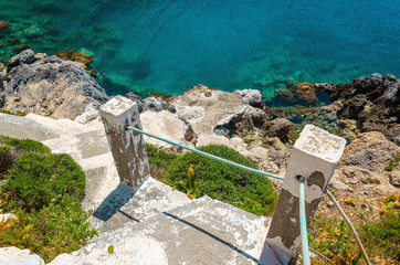 Old stairs from the beach leading to clear azure water in bay on