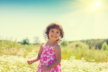 Happy little girl walks on the flower field