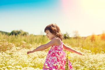 Happy little girl walks on the flower field