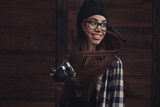 smiling girl in glasses with vintage camera