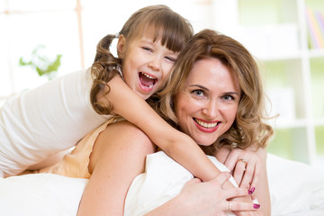 Woman and kid girl in bed playing and smiling