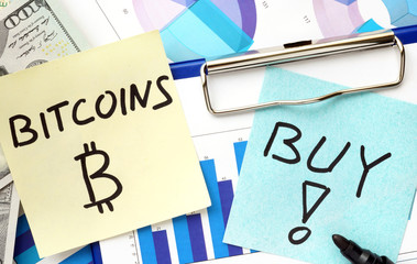 Paper with words bitcoins and buy and graphs.