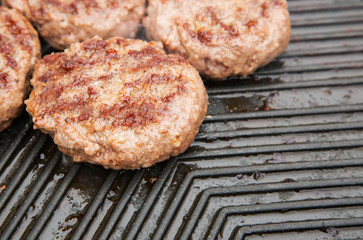 Beef burgers cooking on a metal griddle