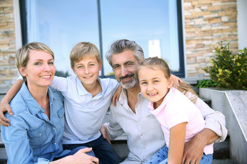 Happy family of four sitting in front of contemporary house