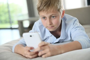 Pre-teenager playing with smartphone laid on couch