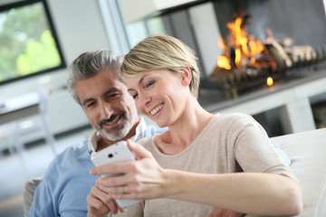 Mature couple at home having fun using smartphone