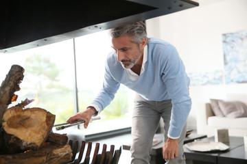 Mature man in contemporary house preparing fire