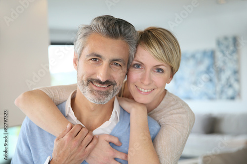 Poster Smiling middle-aged couple standing in brand new home