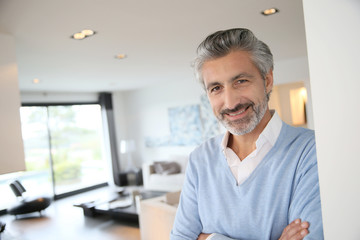 Smiling mature man standing in contemporary house