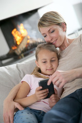Mother and daughter playing together with smartphone