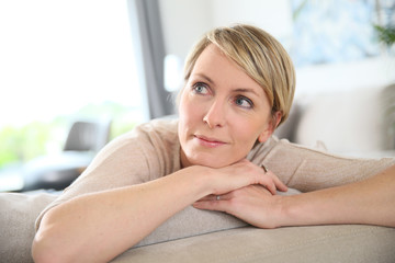 Middle-aged woman relaxing in sofa at home