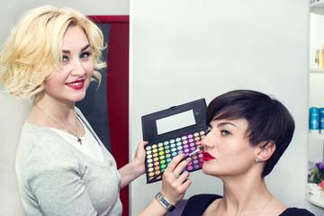 Make-up artist in the studio doing makeup beauty girl