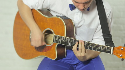 Talented enthusiastic guitarist playing the guitar sitting in