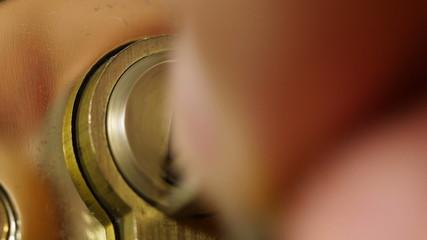 Key sliding into lock and locking\ unlocking door. 4K UHD video.