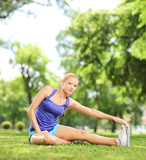 Young female athlete stretching her leg in a park