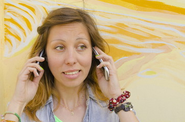 Brunette talking on two mobile phones