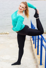Sportive girl doing stretching near the sea