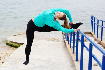 Sportive woman doing stretching near the sea