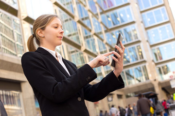 business woman in the street checking her emails