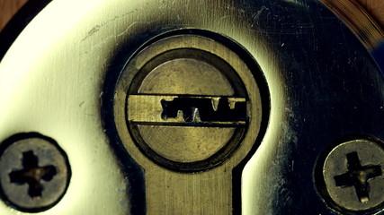 Closeup of house key sliding into lock and locking door.