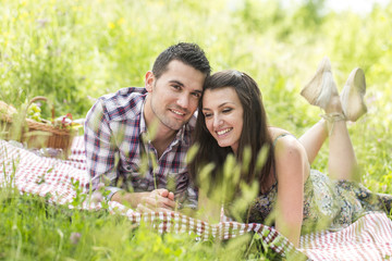 happy couple having a picnic in summer