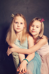 Two Young Sisters Hugging on background