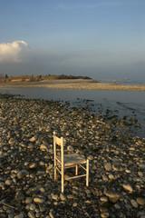 silla abandonada en la orilla del mar