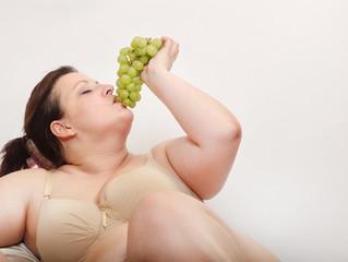 Overweight woman eating fresh sweet grape.