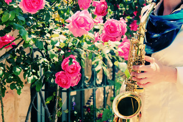 Saxophonist playing on saxophone on pink roses background