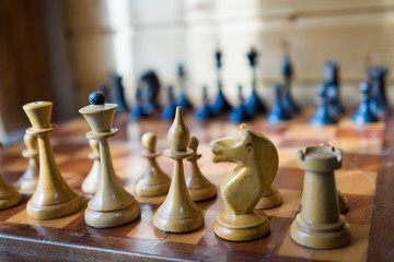 Old Craved wooden Chess pieces on a Board