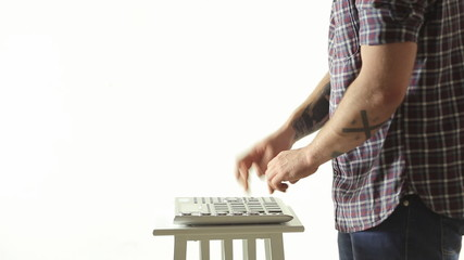 Trendy guy skillfully performs music on Pad Midi Controller