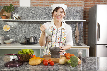 An Asian woman chef cooking with Thai mortar in the kitchen