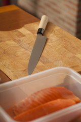 raw fresh piece of salmon fish with Japanese knife