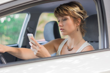 Young woman using mobile phone while driving a car