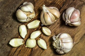 Garlic bulbs and garlic cloves on wooden background