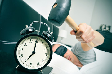 young man in bed about to hammer his alarm clock