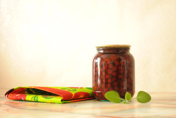 The bank of cherry jam with mint leaf