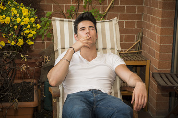 Handsome dark haired young man smoking a cigarette in a balcony