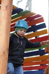 Child with helmet climbing at playground