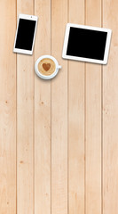 Two gadgets and coffee on a wooden table