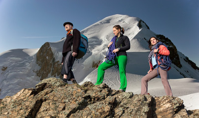 Team of climbers walks on alpine background
