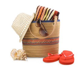 Beach bag and towel with sunbathing accessories on white