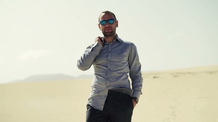 Portrait of happy, young businessman standing on desert